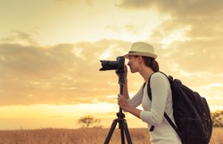Female photographer taking pictures of the beautiful sunset.