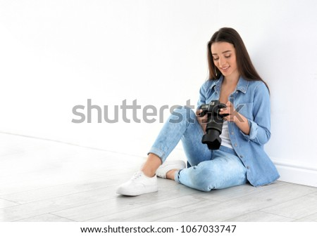 Female photographer with camera sitting on floor near wall indoors #1067033747