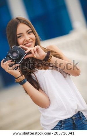 female photographer with professional SLR camera, natural light, selective focus on nearest part of lens with blend. beautiful girl photographed in the old camera