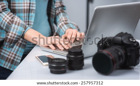 Female photographer working in her studio hands close up and digital camera on foreground