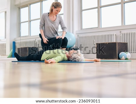 Female physical therapist assisting senior woman with leg exercise in therapy gym. Elder woman lying on floor being assisted by personal trainer in stretching exercises.