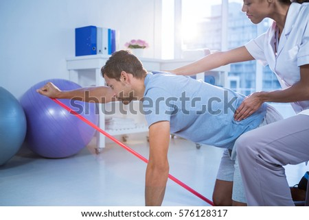 Female physiotherapist assisting a male patient while exercising in the clinic