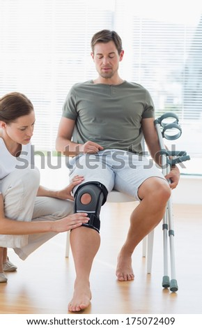 Female physiotherapist examining leg of man with crutches in hospital