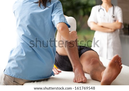 Female physiotherapist helping to exercise the patient injured knee