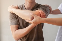 Female physiotherapists provide assistance to male patients with elbow injuries examine patients in rehabilitation centers. Physiotherapy concepts.