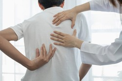 Female physiotherapists provide physical assistance to male patients with back injuries back massages for relaxation and muscle recovery in the rehabilitation center.