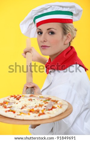Female pizza chef with a wooden peel