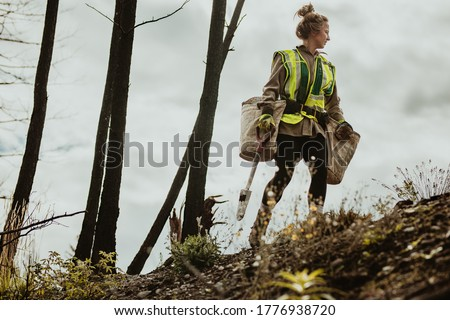 Female planting trees in forest. Woman tree planter wearing reflective vest walking in forest carrying bag full of trees and a shovel. Stock foto ©