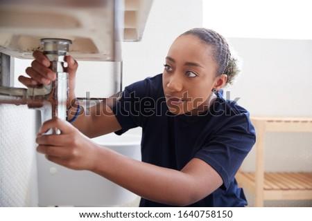 Female Plumber Working To Fix Leaking Sink In Home Bathroom Foto d'archivio ©