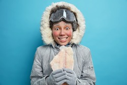 Female polar explorer goes ice fishing during winter time dressed in outerwear holds frozen fish dressed in comfortable outfit over blue wall trembles during cold days prepared for weather changes