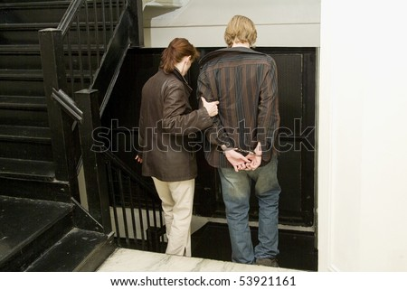 female police officer escorting young man under arrest - stock photo
