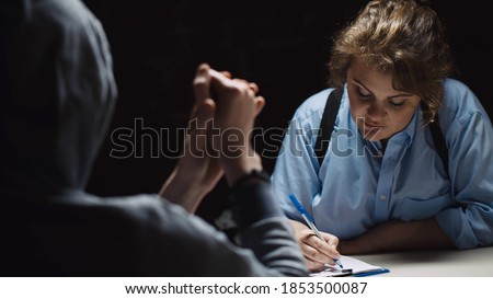 Female police officer interrogating criminal in handcuffs at desk in dark room. Woman cop questioning suspect and writing down information at police department Stock photo ©