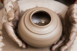 female potter's hands shaping up the terracotta clay pot on wheal.