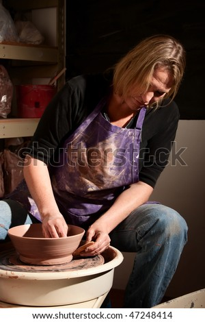 Female potter shaping clay with wooden jigger
