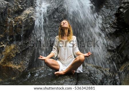 Female Practising Yoga on Waterfall. Stock image.