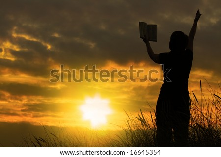 female praying with bible against summer sunset - stock photo