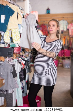 11fa7aa94 Free photos Young pregnant woman choosing baby clothes at baby shop ...