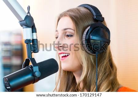 Female presenter or host in radio station hosting show for radio live in Studio