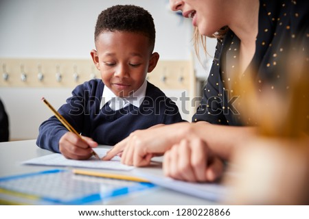 Female primary school teacher helping a young school boy sitting at table in a classroom, close up, selective focus