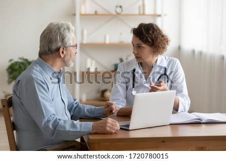 Female professional doctor explaining geriatric disease treatment talking to senior patient at medical visit. Physician consulting examining old man patient in hospital. Elderly health care concept