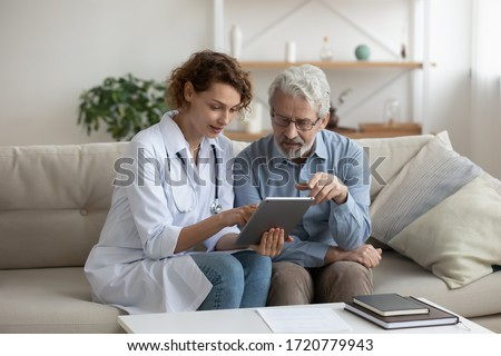 Female professional doctor showing medical test result explaining prescription using digital tablet app visiting senior man patient at home sitting on sofa. Elderly people healthcare tech concept.