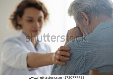 Female professional doctor touching shoulder comforting upset senior patient having geriatric disease expressing trust, support concept. Geriatrician helping lonely elderly crying man. Close up view