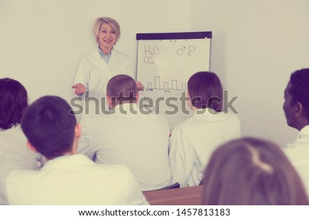 Female professor giving presentation for medical students in lecture hall  #1457813183