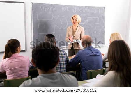 Female professor standing in front of students and lecturing them