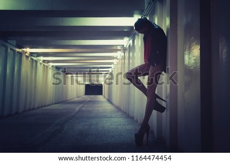 Female prostitute working on the night street. sexy girl stands at the wall in the tunnel bending her leg in a seductive pose.