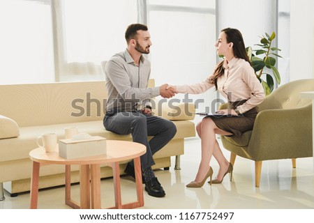 female psychiatrist and patient shaking hands in office #1167752497