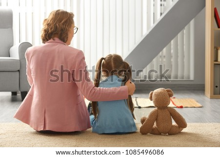Female psychologist calming cute little girl in office
