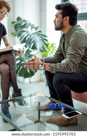 Female psychologist consulting indian man, writing notes during psychological therapy session