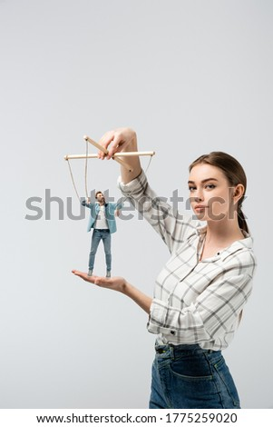 female puppeteer holding male marionette isolated on grey Stockfoto ©