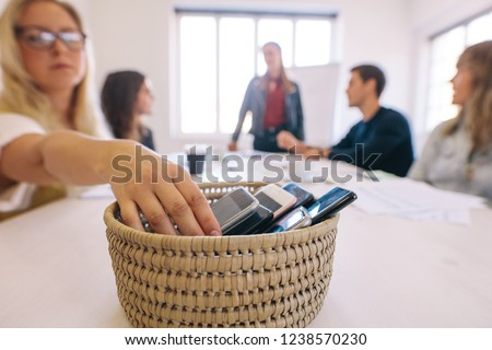Female putting her cell phone in a basket while attending a board room meeting in her office. No cellphone zone at workplace meeting.