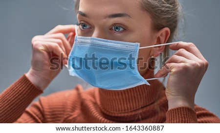 Female putting on medical protective mask to health protection and prevention during flu virus outbreak, epidemic and infectious diseases Foto d'archivio ©