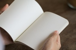 Female reading an empty open book on a desk, Insert your dsign or message on empty space.