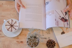 Female reading magazine and drink coffee on wooden table from above