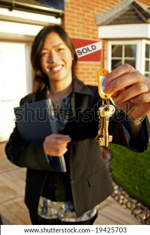 Female real-estate agent holding keys to a new property