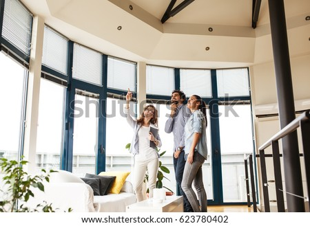 Female Real Estate agent offer home ownership to young couple. #623780402