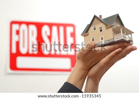 Female real estate agent's hands offering a home for sale