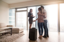 Female real estate agent showing property to young interested couple travellers, just arrived with baggage, tenants moving in or out rented apartment, renting flat on trip, daily rent abroad