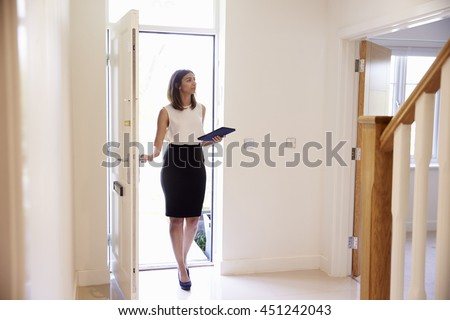 Female Realtor In Hallway Carrying Out Valuation
