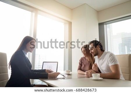 Female realtor meeting with young couple in real estate agency office. Discussing first property investment with broker, construction company manager showing build project, apartment plan on a laptop