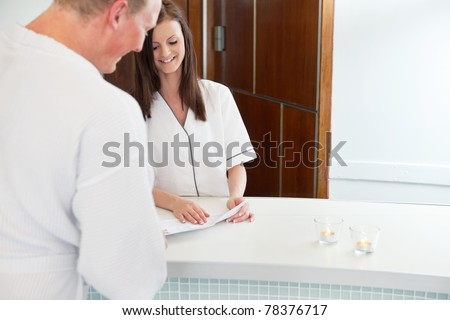 Female receptionist and male customer at sauna reception desk