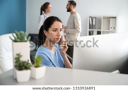 Female receptionist talking by phone in clinic Stock photo ©