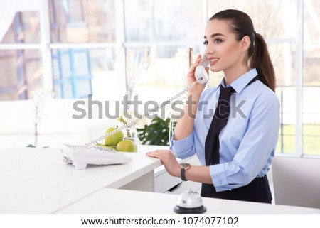 Female receptionist talking on phone at workplace in hotel #1074077102