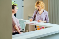 Female receptionist working with visitor in medical office. Visitor read and write signature in document at reception of clinic. Blond woman near reception desk in clinic