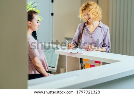 Female receptionist working with visitor in medical office. Visitor read and write signature in document at reception of clinic. Blond woman near reception desk in clinic Foto stock ©