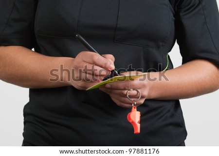 female referee writing on the card