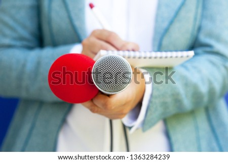 Female reporter at press conference, taking notes, holding microphone #1363284239
